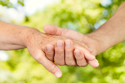 Closeup of old people hands holding together outdoor.